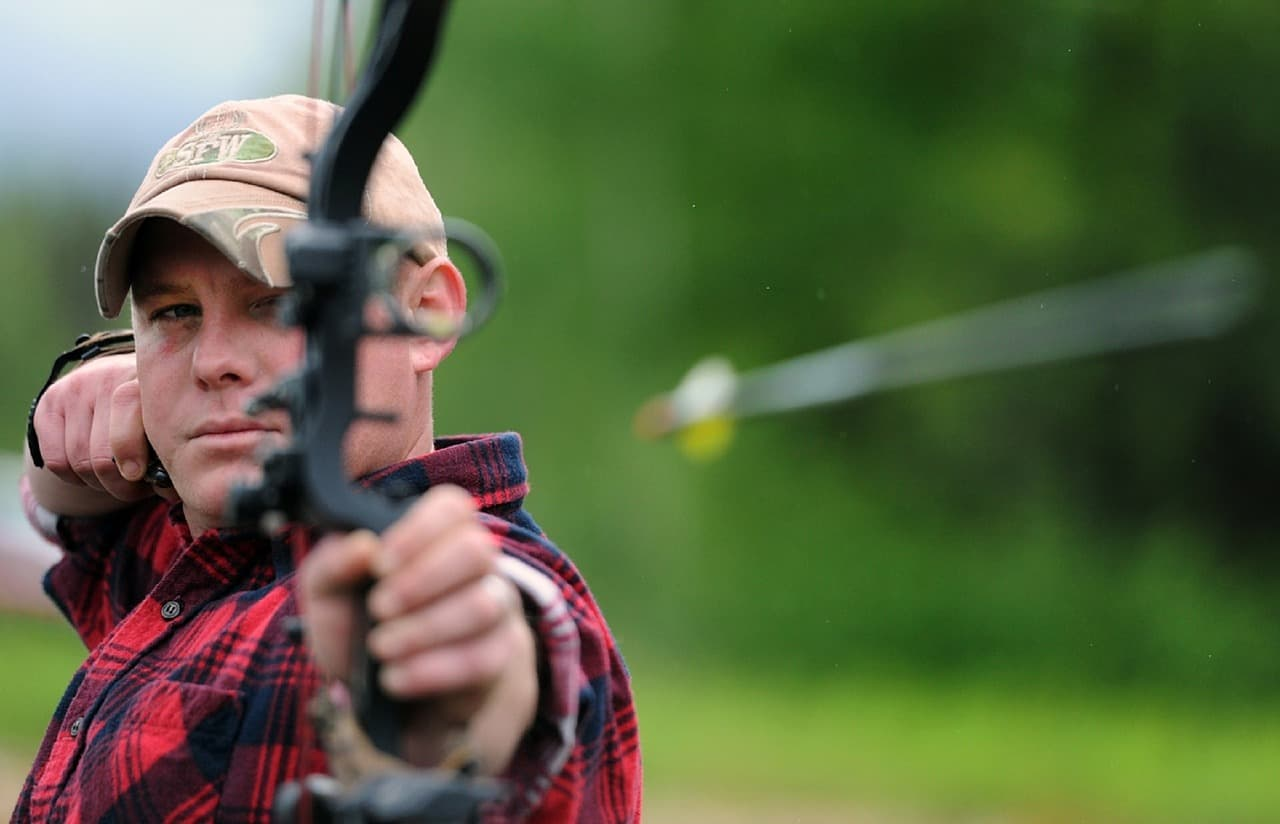 In this image a guy is playing archery metaphorically meaning that keep your health goals on target Top 10 health and fitness tips