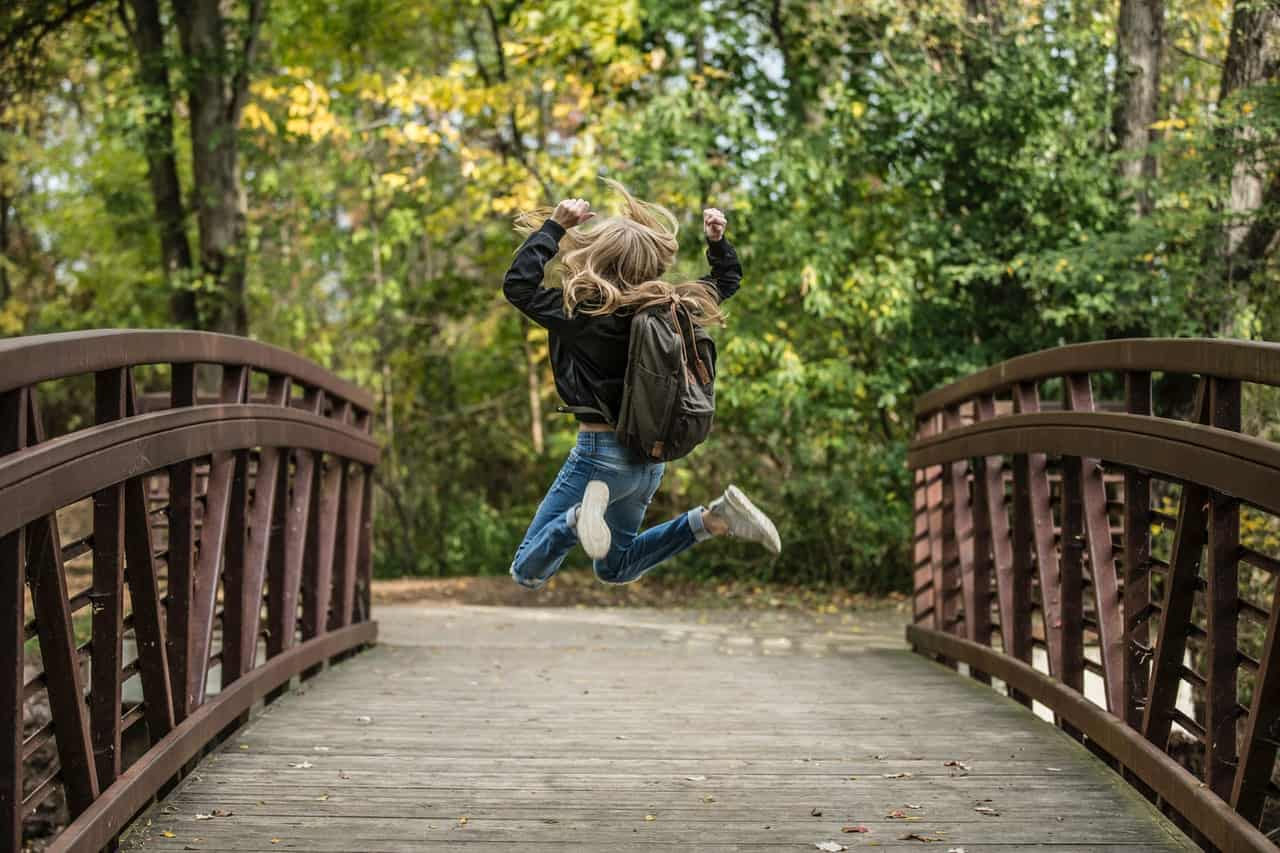 girl jumping on a bridge What is more important Health or Success